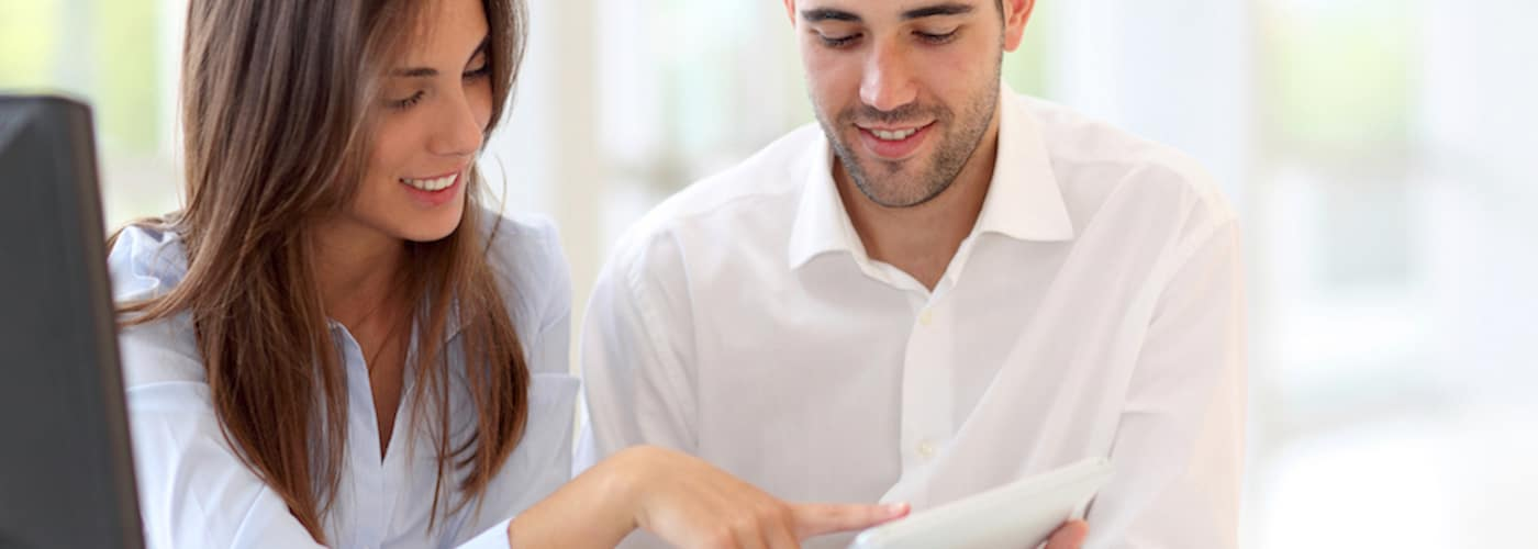 couple at home looking at touchpad