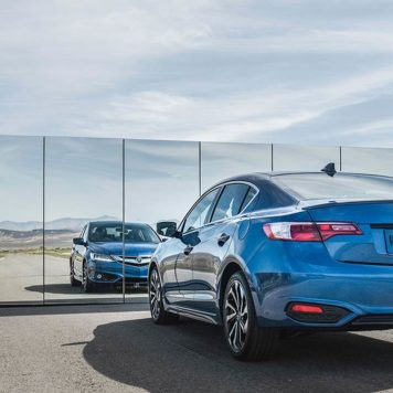 Blue ILX parked in front of chain link fence