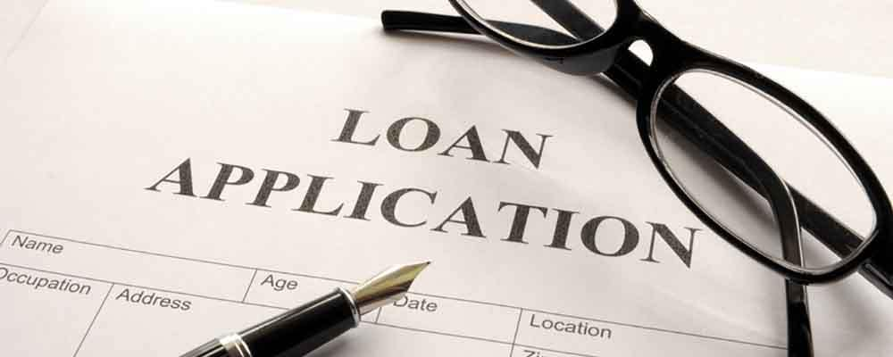 Loan Application with glasses sitting on top