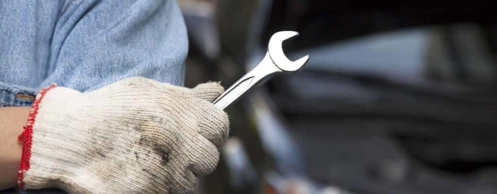 Mechanic wearing gloves and holding a wrench