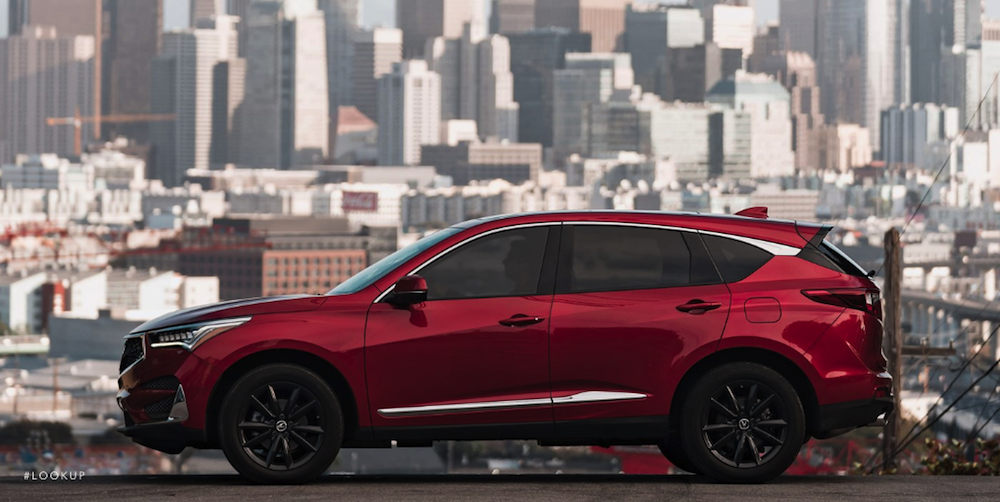 red 2019 Acure RDX SUV with city skyline
