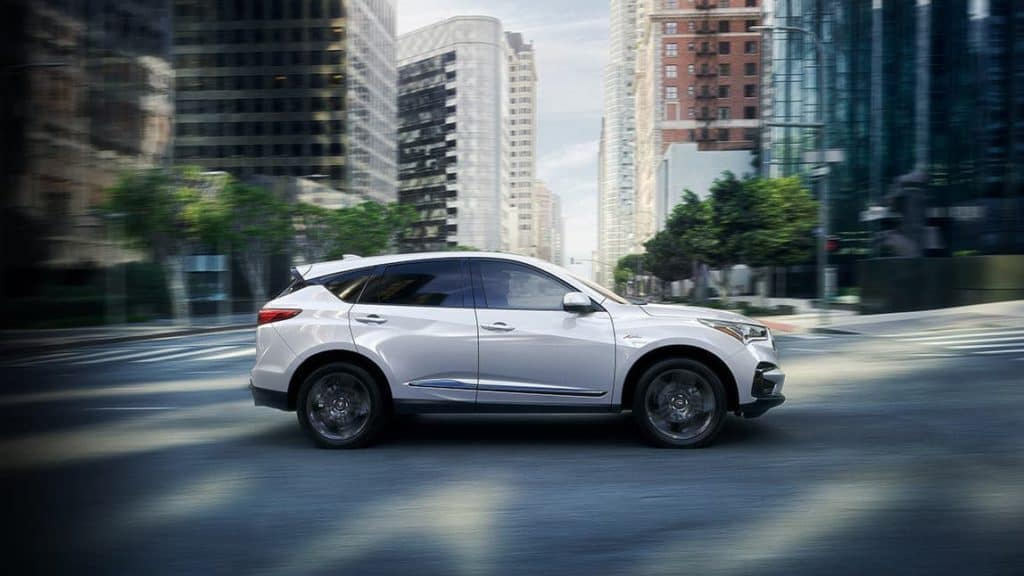 2020 Acura RDX platinum white pearl driving in a city profile view