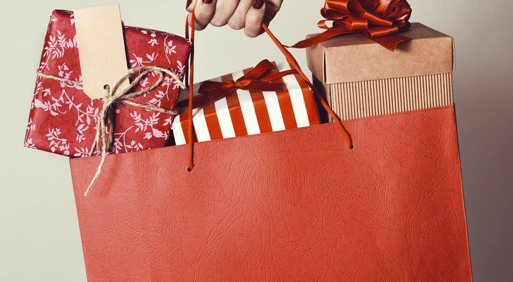 A shopping bag is shown with wrapped gifts.