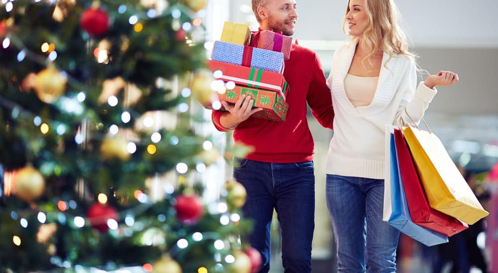 A couple is holiday shopping in Mesa, AZ, with a Christmas tree in front of them.