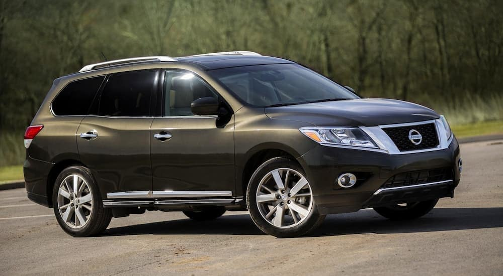 A dark green 2015 Nissan Pathfinder is parked in front of trees.