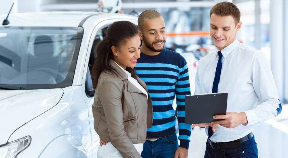 A salesman is going over information on used cars for sale with a couple.