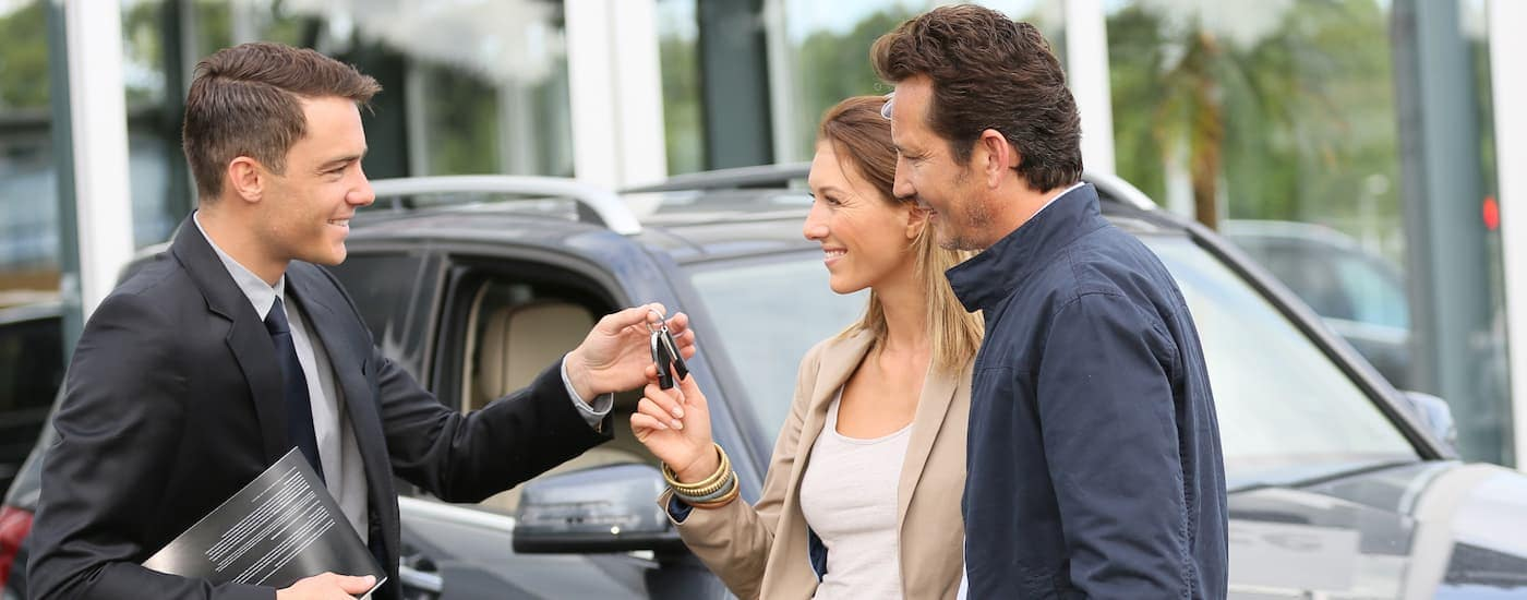 A salesman is handing keys to a couple at a car dealership near me.