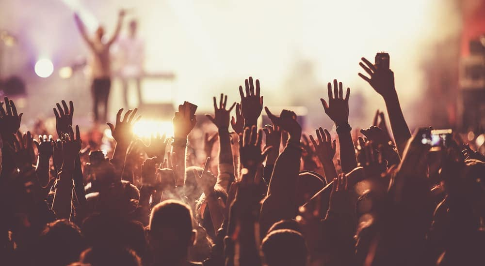 A crowd has hands up at a music festival in Mesa, AZ.