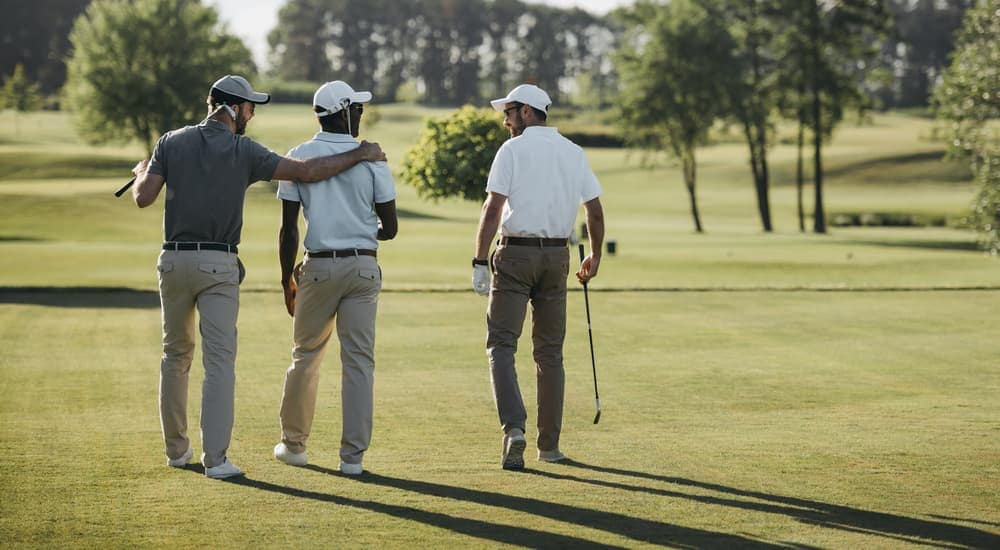Three friends are walking on a golf course.