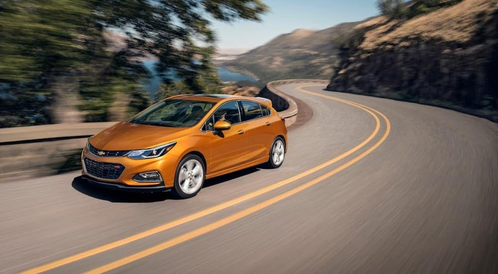 An orange 2018 Chevy Cruze, popular among used cars, is driving around a corner.