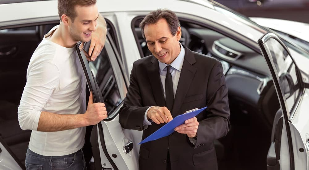 A salesman is showing a buyer a vehicle report while looking at used cars in Mesa, AZ.
