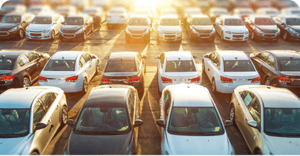 Used call to action image of a lot full of sedans with the sun setting over the vehicles