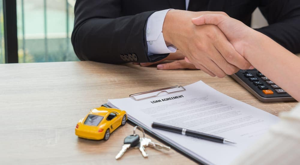 A salesman is shaking a customer's hand above a desk with car keys, a yellow toy car, calculator and a signed the bad credit auto loan