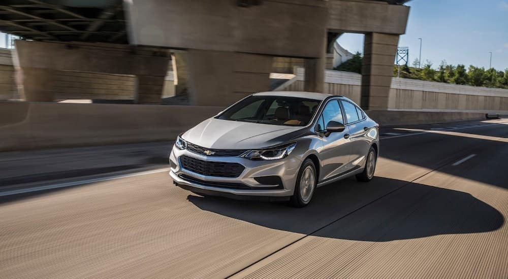 A silver 2017 Chevy Cruze is driving on a highway near Mesa, AZ.