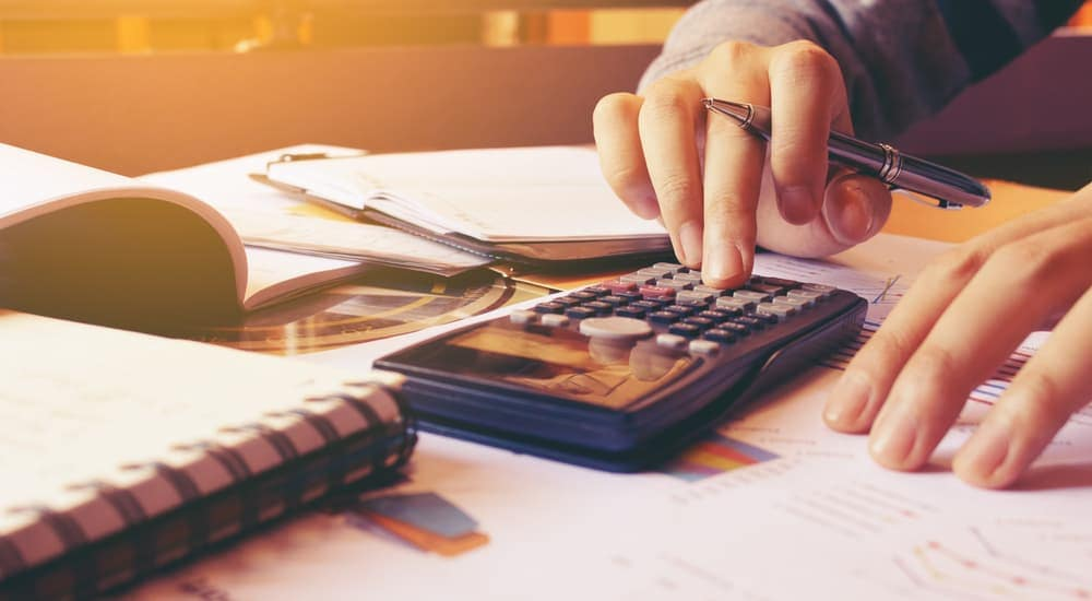 A close up of someone figuring out their budget on a calculator with papers and books on a desk.