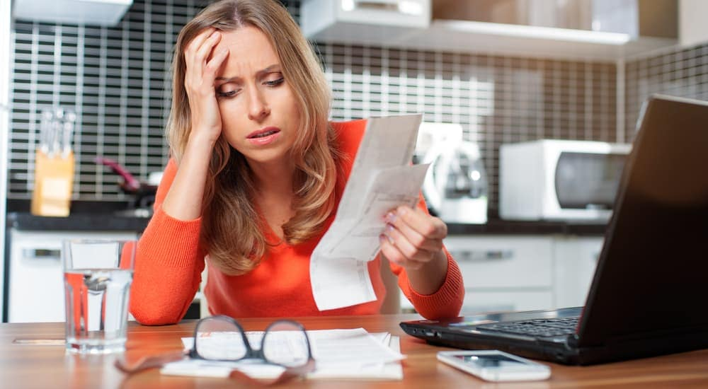 A woman is upset while looking at her finances and wondering about bad credit auto loans.