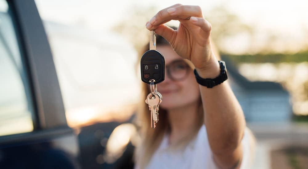 A woman is holding up the keys to her car after leaving a car dealership near me in Mesa, AZ.