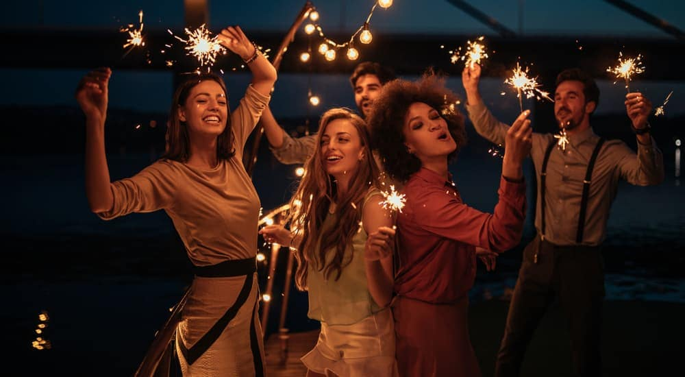 A group of friends in Mesa, AZ, are dancing at night with sparklers.