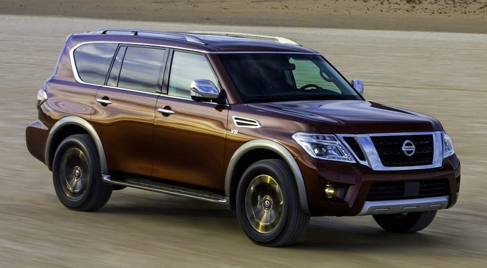 A burgundy 2017 Nissan Murano, popular among Mesa, AZ, used cars, is driving in the desert.