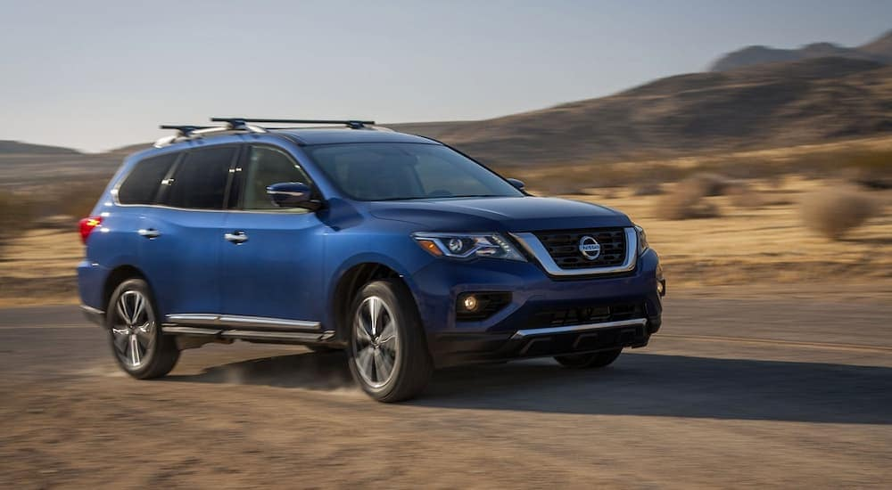 A blue 2017 Nissan Pathfinder is driving through the desert.
