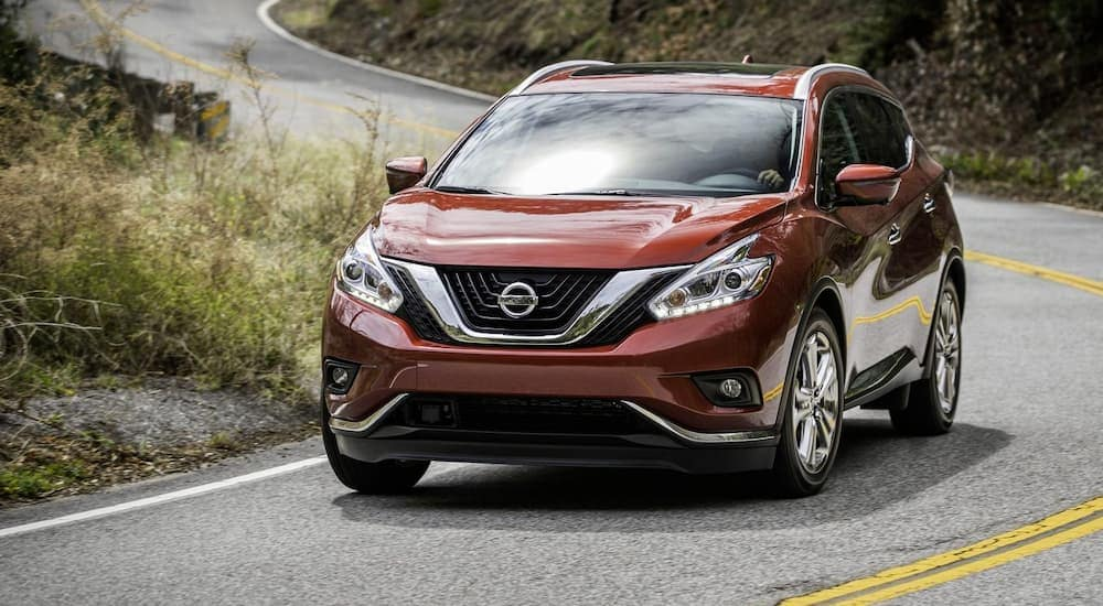 A red 2018 Nissan Murano is driving on a winding road.