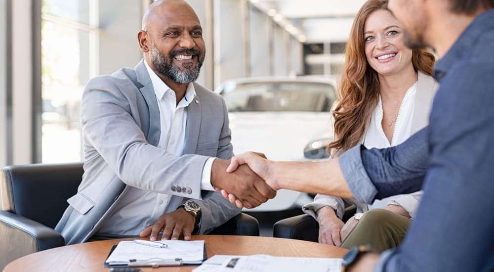 A salesman is shaking hands with a couple after buying a used car.