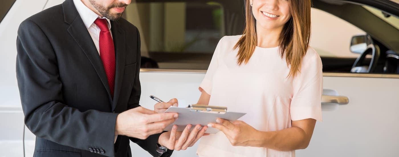 A salesman is going over paperwork on a clipboard with a woman.