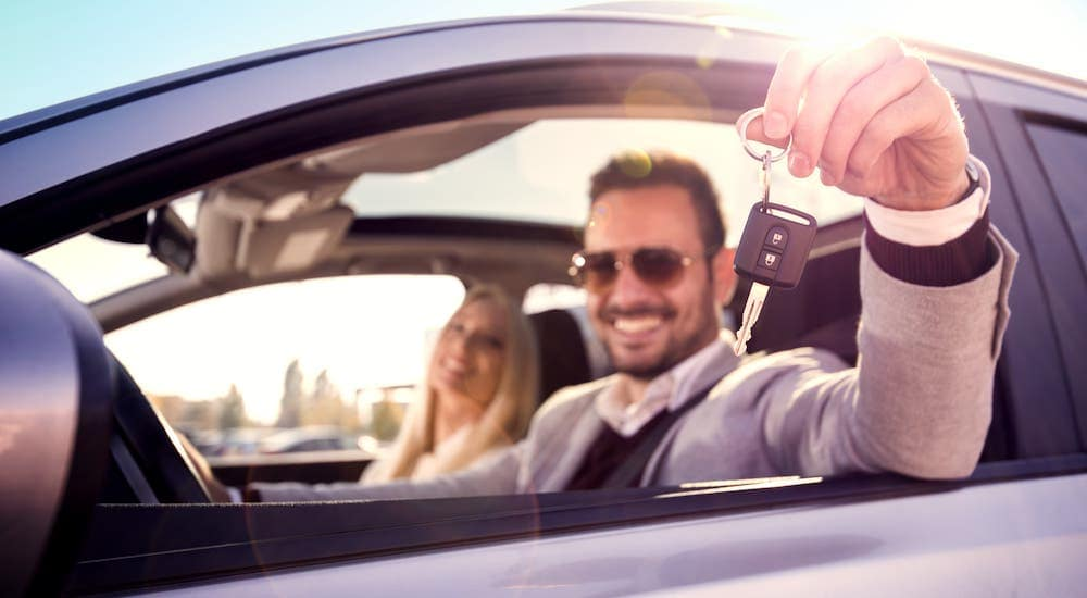 A couple is smiling from the inside of their newly purchased used car.