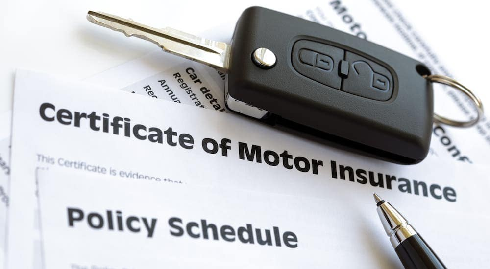 A car key and pen are sitting on top of a certificate of Motor Insurance.