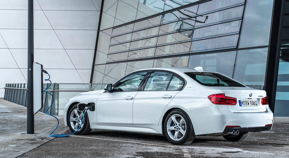 A white 2016 BMW 330e iPerformance is charging outside a Mesa, AZ, building.