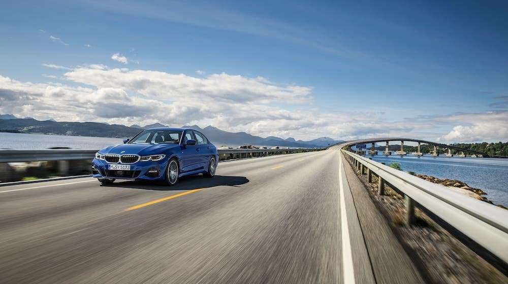 A blue 2019 BMW 3 Series is driving over a bridge.