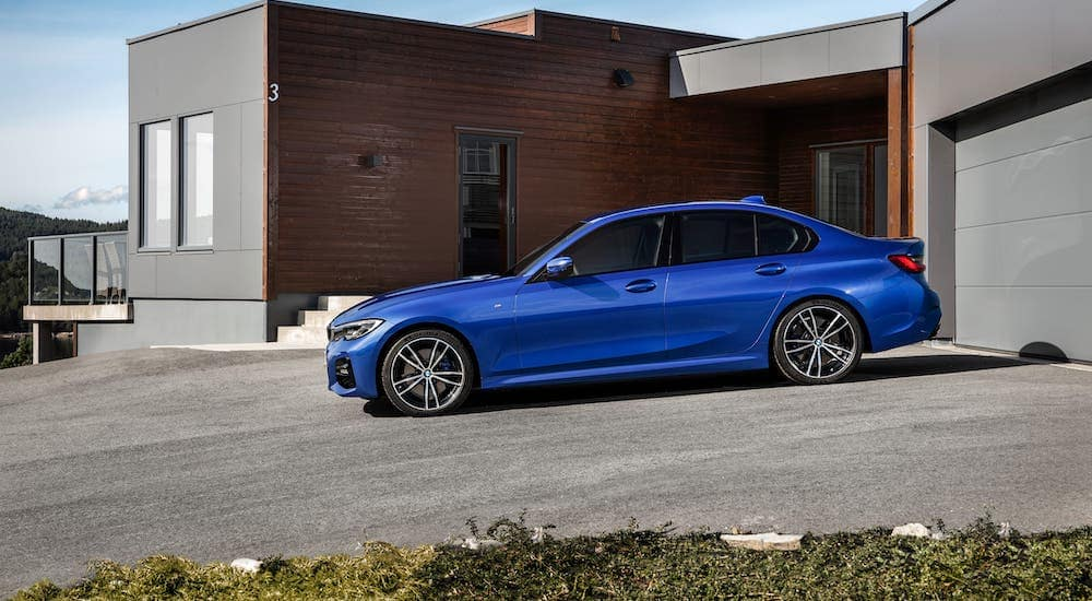 A popular used car for sale, a blue 2019 BMW 3 Series, is parked in front of a modern home.