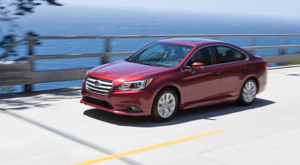 A red 2016 Subaru Legacy Premium is driving on a bridge in front of water.