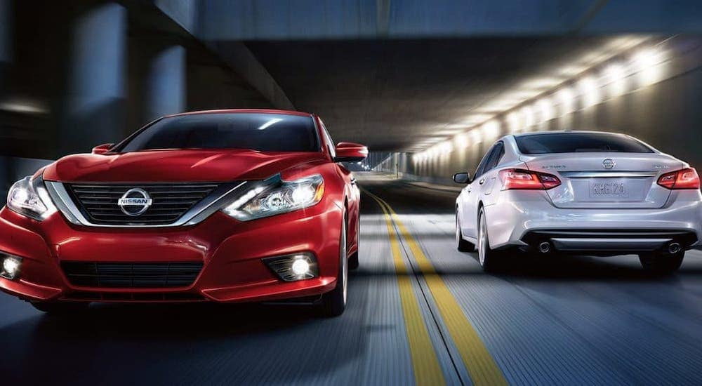 A red and a white 2018 Nissan Altima are passing one another in a tunnel at night.