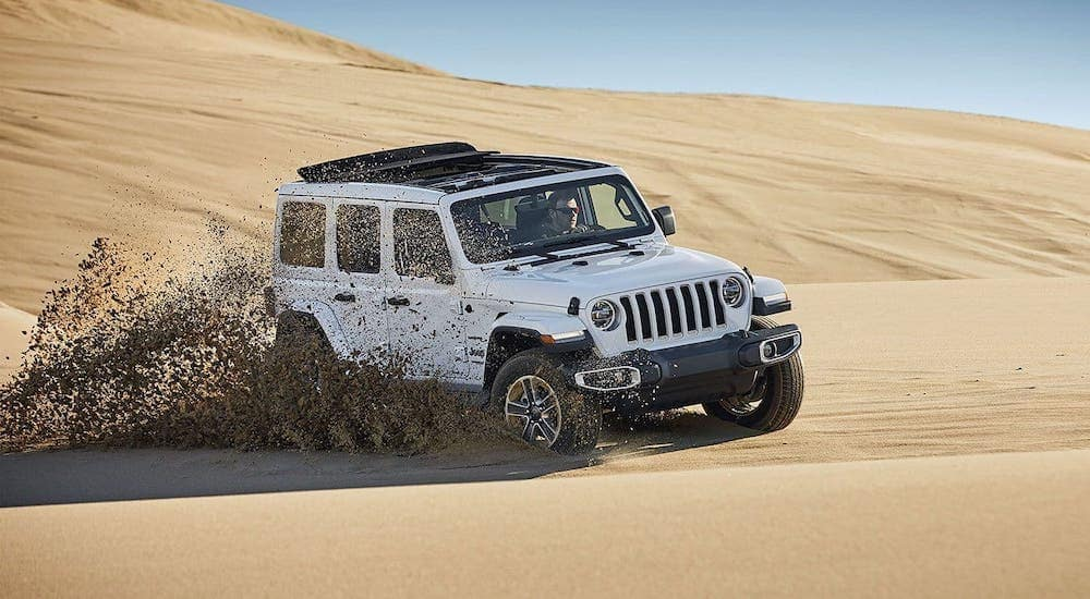 A white 2019 Jeep Wrangler Unlimited is driving through sand dunes outside Mesa, AZ.