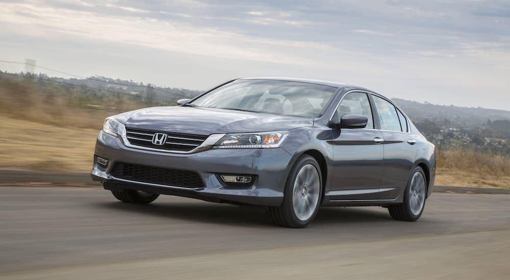 A grey 2015 Honda Accord is driving past yellowed grass.