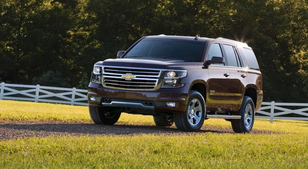 A dark brown 2016 Chevy Tahoe is parked in a field.