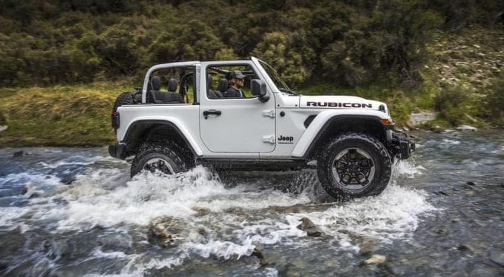 A white 2018 Jeep Wrangler, which is popular among used cars for sale, is crossing a river while off-roading.