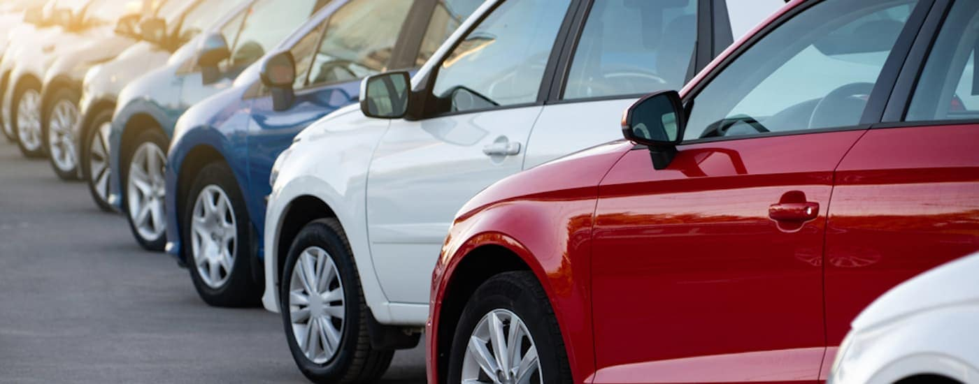 A row of vehicles at a used car dealership is shown.