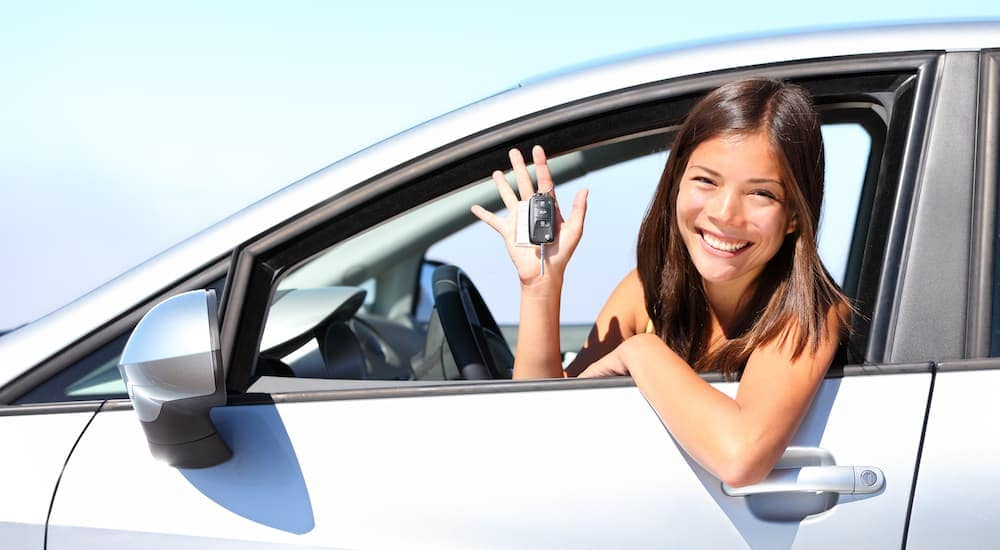 A woman is holding up the keys to her silver car after leaving a used car dealership in Mesa, AZ.