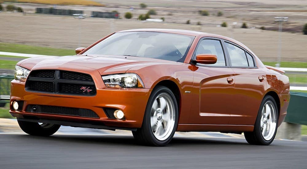 An orange 2011 Dodge Charger RT is driving on a highway near Mesa, AZ.