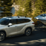 White 2020 Toyota Highlander towing boat through wooded lake highway