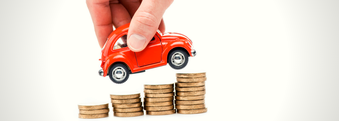 A tiny car climbing a small stack of coins. Sell your car with Gurnee Volkswagen