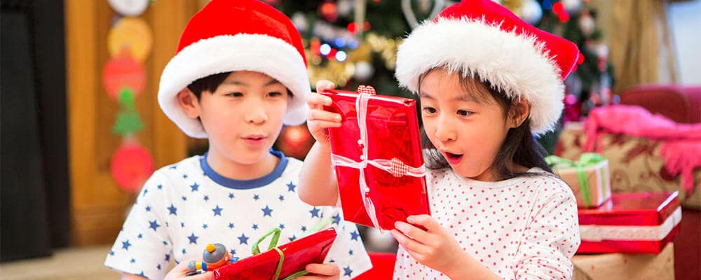 Two children in Santa hats with gifts