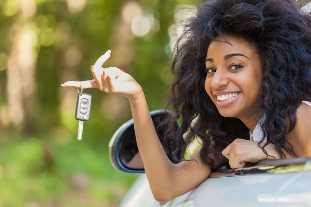 Woman holding keys to her new car