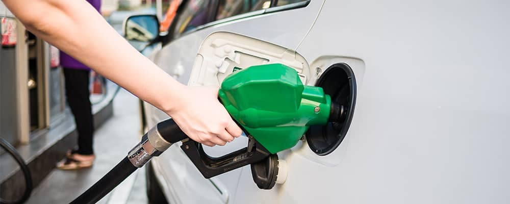 Person filling gas tank of car