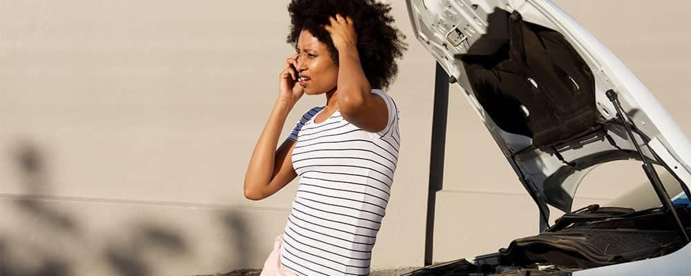 Car breakdown woman on phone hood open
