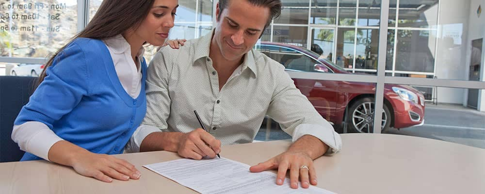 Man and Woman Sign Paperwork at Dealership