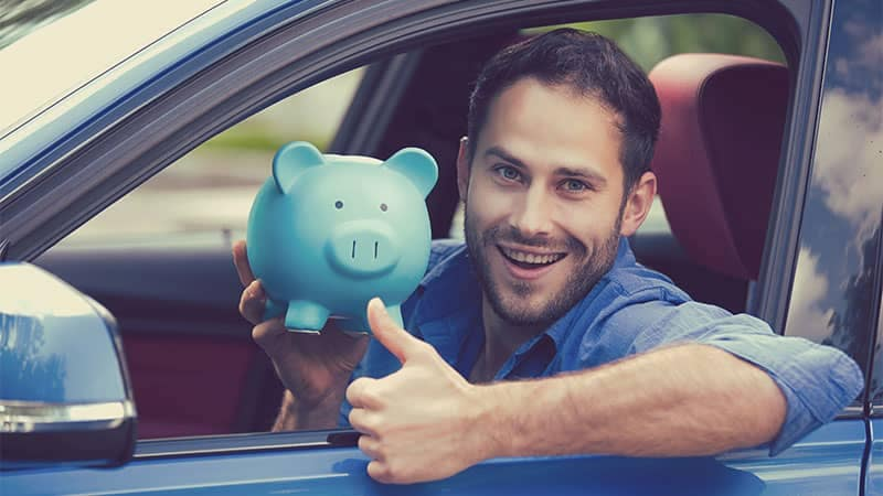 Man gives thumbs up with piggy bank in car