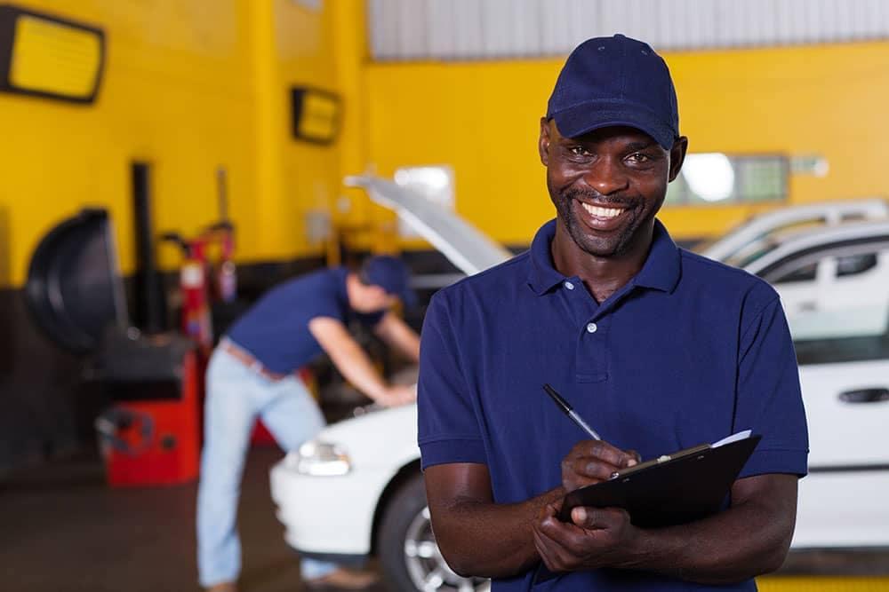 Service technician with car checklist